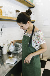 Barista pouring milk in coffee while standing in kitchen at coffee shop - XLGF00601