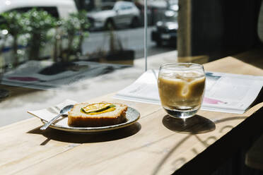 Cold brew coffee and cake on table at coffee shop - XLGF00604