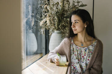 Young woman with lemonade glass looking through window while sitting at coffee shop - XLGF00613