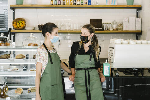 Businesswomen wearing face mask and apron standing by counter at coffee shop - XLGF00616