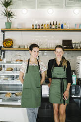 Smiling businesswomen standing by counter at coffee shop - XLGF00619