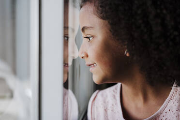 Close-up of cute girl looking through window at home - EBBF00927