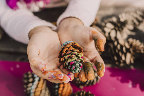 Messy hands of girl with colorful pine cone at picnic table in park - ERRF04614