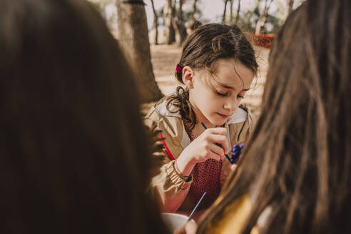 Cute girl decorating pine cone with sisters at park - ERRF04617