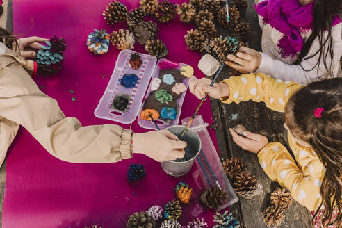 Girls decorating pine cones while coloring at picnic table in park - ERRF04623