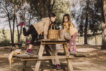 Girls with wicker baskets at picnic table in park - ERRF04632