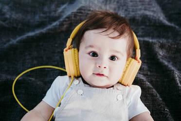 Baby boy wearing headphones lying on blanket outdoors - EBBF00987