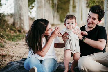 Smiling parents playing with baby boy while sitting on blanket outdoors - EBBF00993