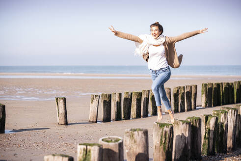 Cheerful young woman with arms outstretched running amidst wooden posts at beach during sunny day - UUF21755