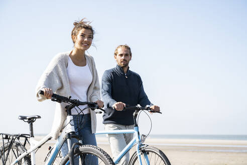 Young couple walking with bicycles at beach against clear sky on sunny day - UUF21761