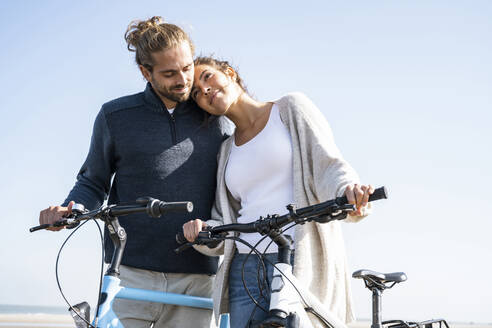 Beautiful woman with head on boyfriend's shoulder standing with bicycles at beach against clear sky on sunny day - UUF21764