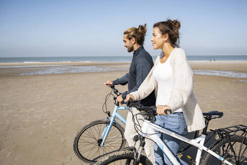 Young boyfriend and girlfriend walking with bicycles at beach against clear sky on sunny day - UUF21767