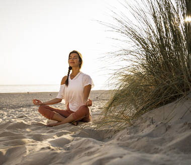 Beautiful young woman practicing yoga while sitting by plant on sand at beach against clear sky during sunset - UUF21770