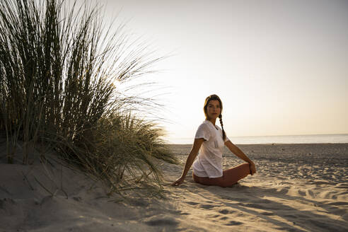 Beautiful young woman practicing yoga while sitting by plant at beach against clear sky during sunset - UUF21773
