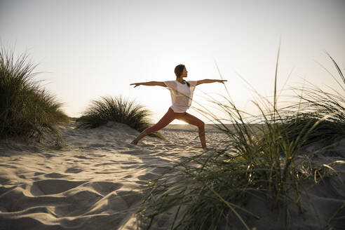 Young woman practicing warrior 2 position yoga amidst plants at beach against clear sky during sunset - UUF21779