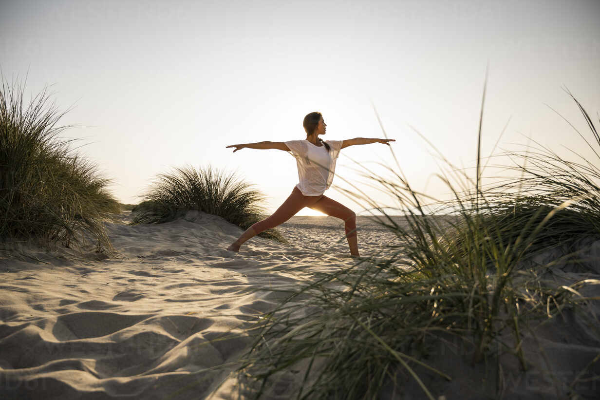 Young woman practicing warrior 2 position yoga amidst plants at beach against clear sky during sunset - UUF21779 - Uwe Umstätter/Westend61