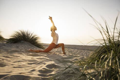 Young woman practicing yoga on sand at beach during sunset - UUF21782