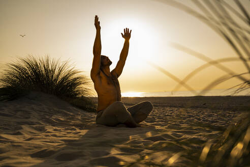 Shirtless young man practicing yoga while sitting with arms raised on sand at beach against clear sky during sunset - UUF21788