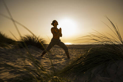 Shirtless young man practicing warrior position yoga with hands clasped at beach against clear sky during sunset - UUF21791