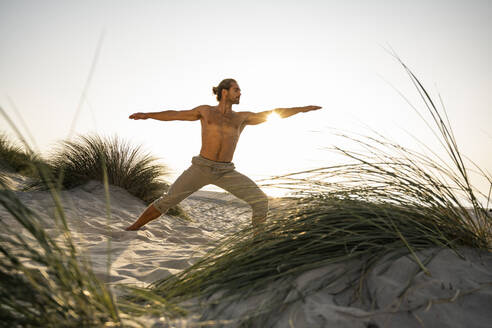 Shirtless young man practicing warrior 2 position yoga at beach against clear sky during sunset - UUF21794