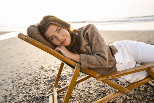 Beautiful young woman relaxing while reclining on folding chair at beach during sunset - UUF21806