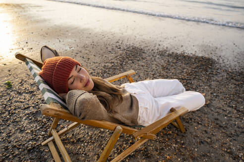 Young woman relaxing on folding chair at beach during sunset - UUF21809
