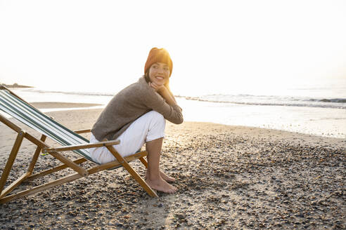 Smiling young woman sitting on folding chair while looking away at beach against clear sky during sunset - UUF21812