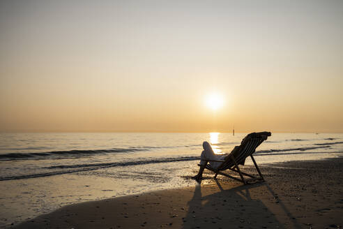Young woman relaxing while sitting on folding chair at beach against clear sky during sunset - UUF21818