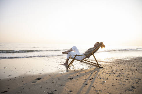 Smiling young woman relaxing while sitting on folding chair at beach against clear sky during sunset - UUF21821