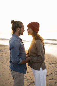Romantic young couple looking at each other while standing on shore during sunset - UUF21833