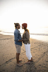 Romantic young couple looking at each other while holding hands standing on shore during sunset - UUF21836