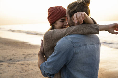Smiling young woman embracing boyfriend while standing at beach during sunset - UUF21845