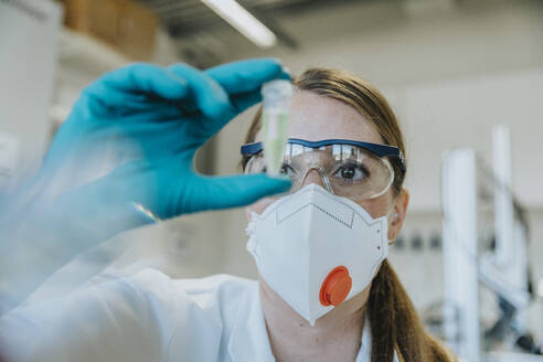 Young woman wearing protective face mask and eyeglasses examining test tube at laboratory - MFF06451