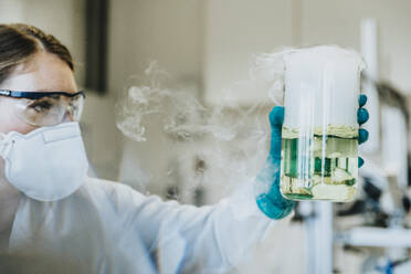 Laboratory assistant wearing protective face mask and eyeglasses holding liquid beaker while standing at laboratory - MFF06454