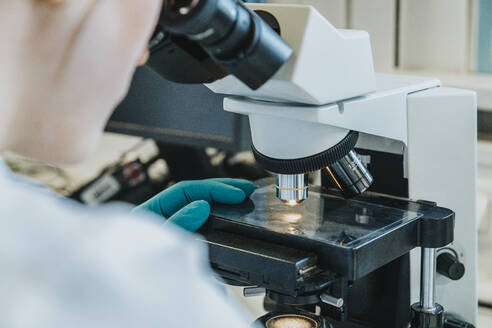 Young woman analyzing human brain microscope slide under microscope while sitting at laboratory - MFF06493