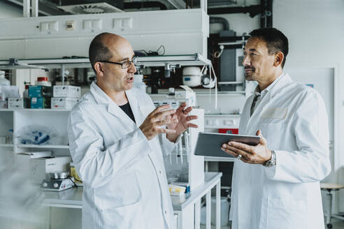 Scientists discussing while using digital tablet at laboratory - MFF06535