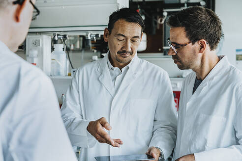 Male scientists using digital tablet while standing at laboratory - MFF06538