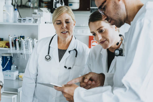 Male and female scientist using digital tablet while standing at laboratory - MFF06541