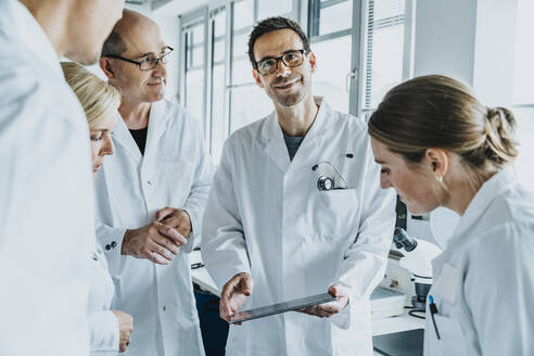 Smiling scientist holding digital tablet while standing by coworkers at laboratory - MFF06547