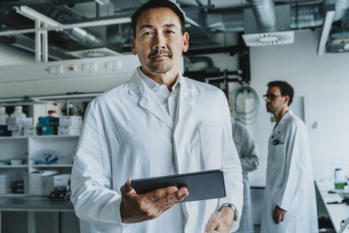 Scientist using digital tablet while standing with coworker in background at laboratory - MFF06556