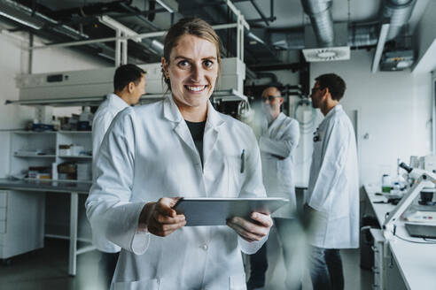 Smiling woman using digital tablet while standing with coworker in background at laboratory - MFF06559