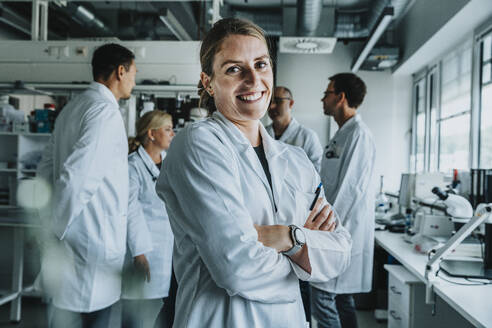 Smiling woman with arms crossed standing with coworker in background at laboratory - MFF06562