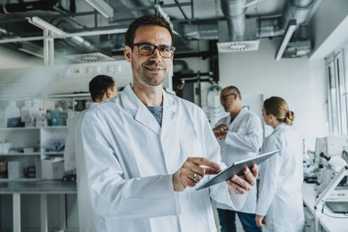 Smiling male scientist using digital tablet while standing with coworker in background at laboratory - MFF06568