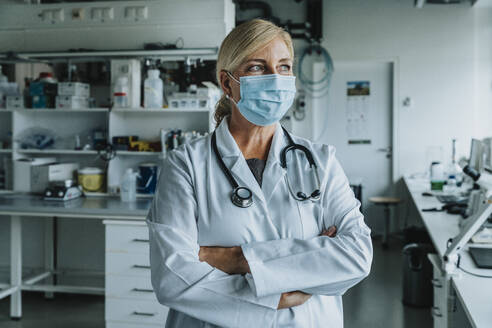 Female scientist wearing face mask standing with arms crossed at laboratory - MFF06574