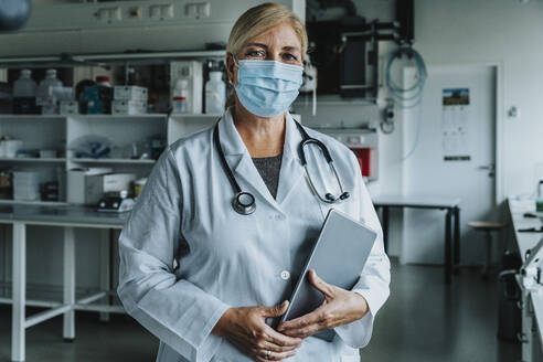 Scientist wearing face mask holding digital tablet while standing at laboratory - MFF06577