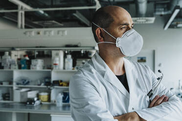 Male scientist wearing face mask looking away while standing with arms crossed at laboratory - MFF06586