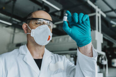 Scientist with protective face mask and eyeglasses holding vaccine bottle while standing at laboratory - MFF06589