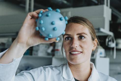 Smiling young scientist holding coronavirus model while standing at laboratory - MFF06592