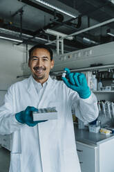 Smiling scientist holding vaccine while standing at laboratory - MFF06595