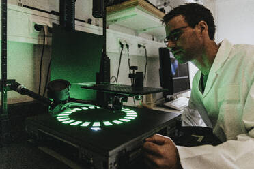 Scientist examining human brain slide on microscope while standing at laboratory - MFF06607